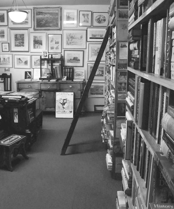 home-library-with-books-and-framed-pictures-in-black-and-white