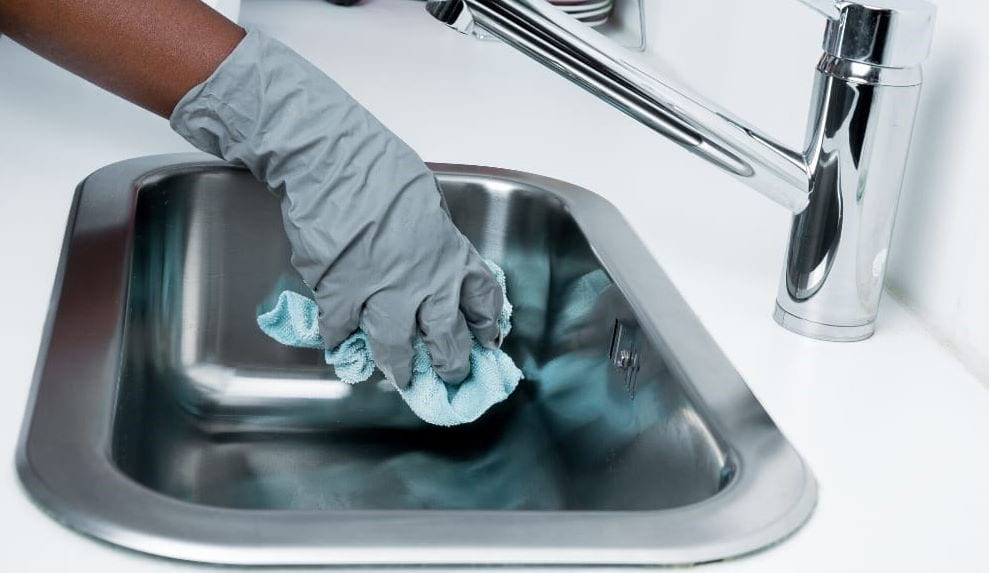 polishing-kitchen-sink-with-microfibre-cloth-and-glove-on